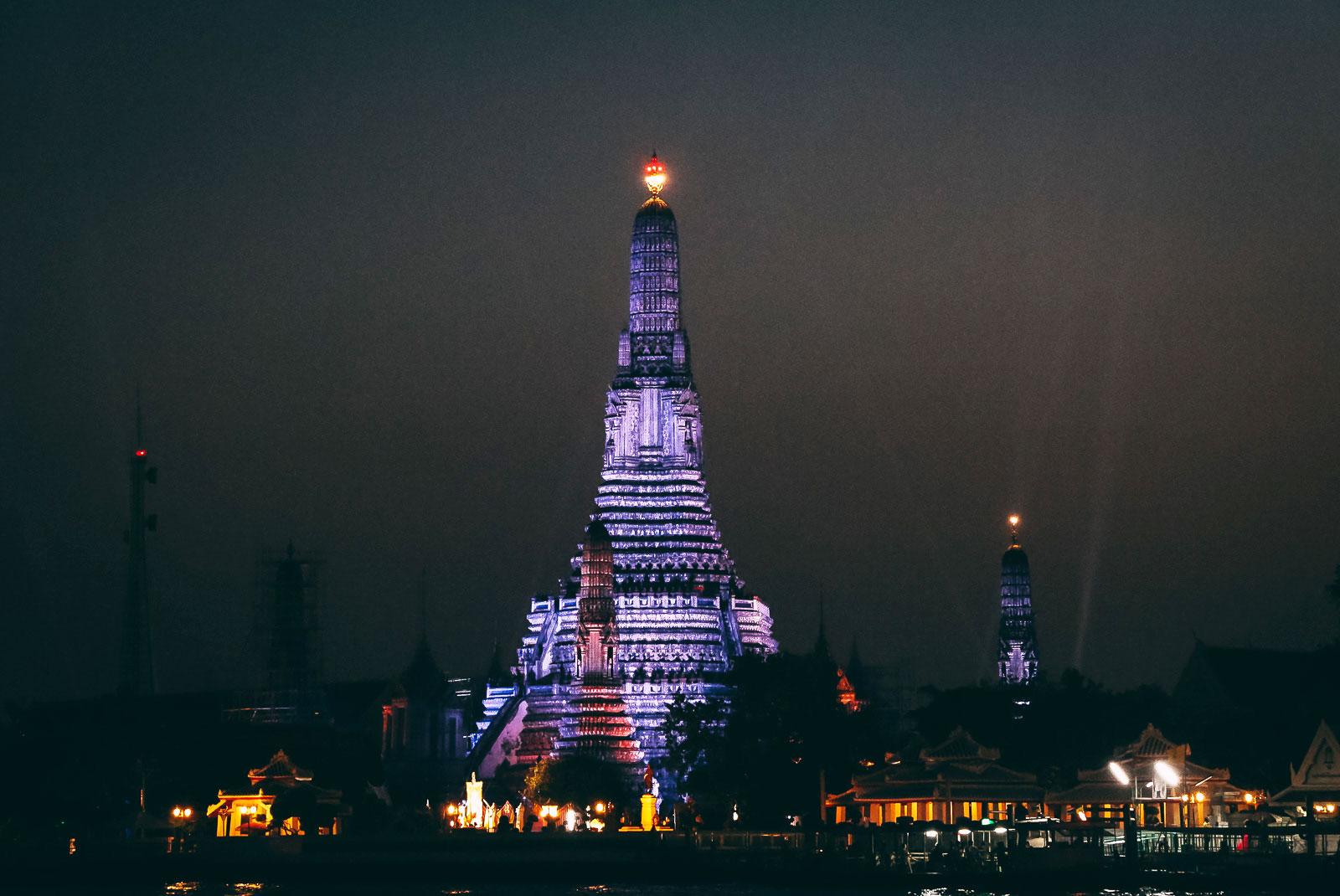 Der Wat Arun wird nachts in unterschiedlichen Farben angestrahlt.