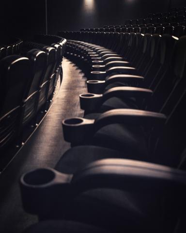 Blick durch eine Sitzreihe im Kino
