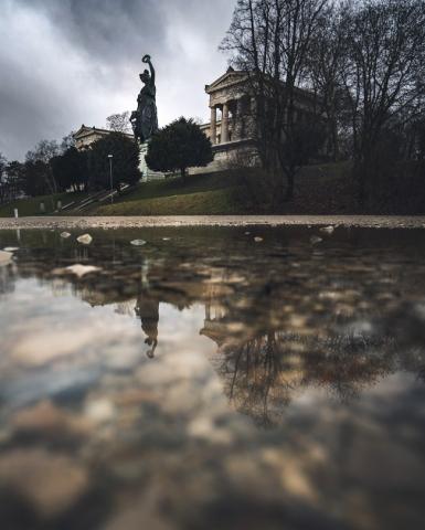 Die Bavaria auf der Theresienwiese in München spiegelt sich in einer Pfütze