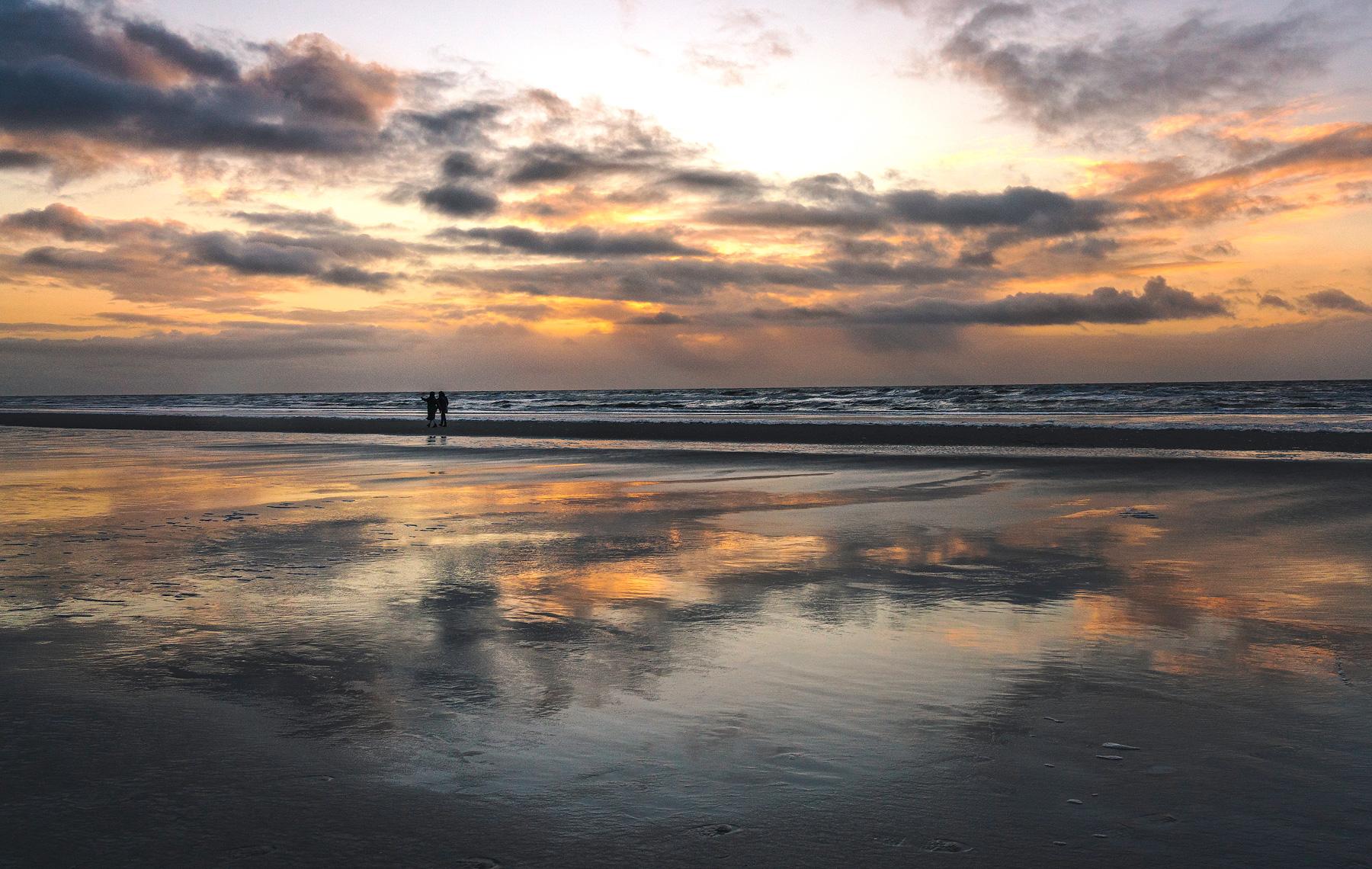 Spiegelungen im Sonnenuntergang am Strand von Sankt Peter-Ording, Deutschland