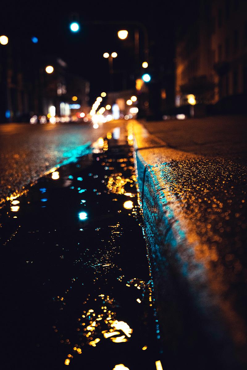 Bordsteinkante, die regennass glänzt. München bei Nacht.