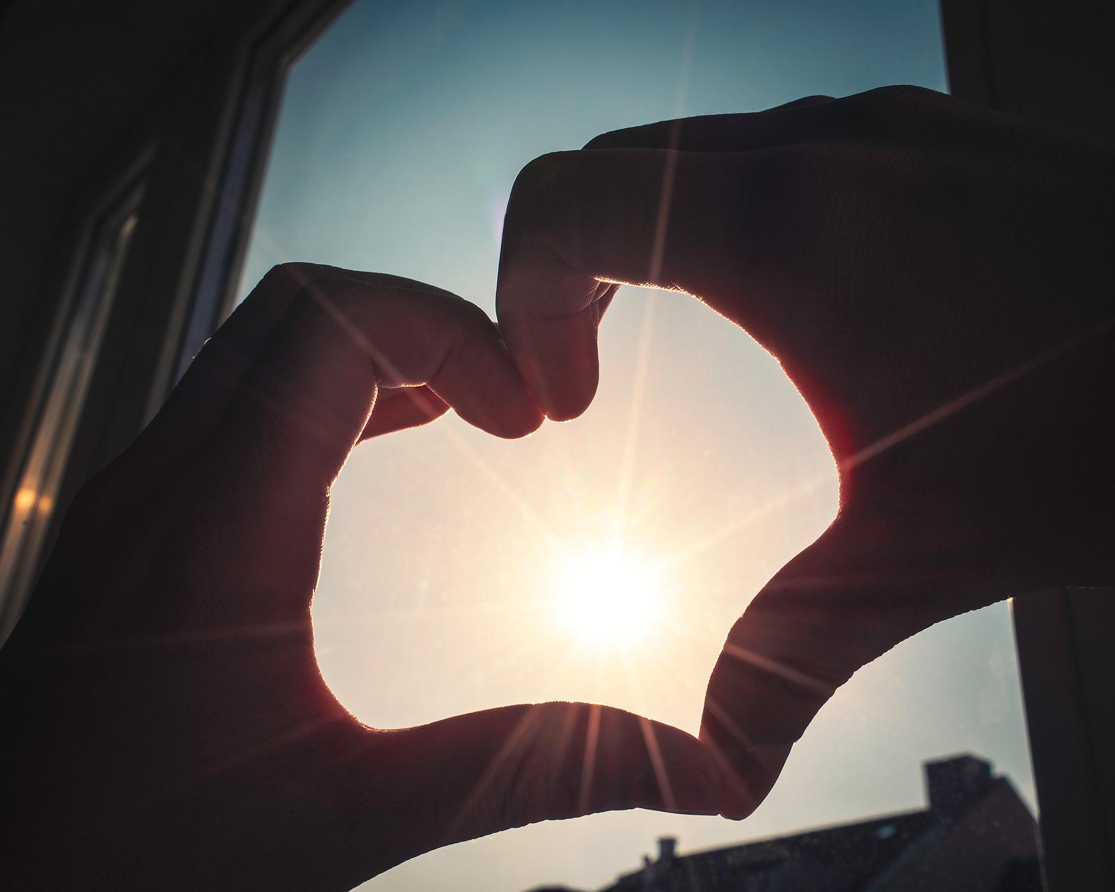 Hände formen ein Herz, die Sonne scheint hindurch